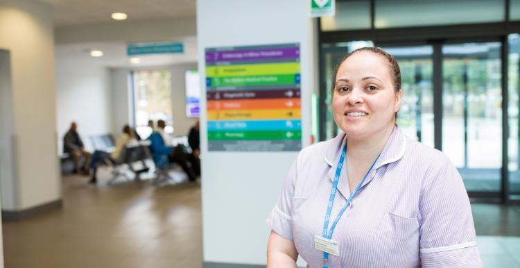 A healthcare worker standing in front of a pillar. We can see a waiting room with people behind her.