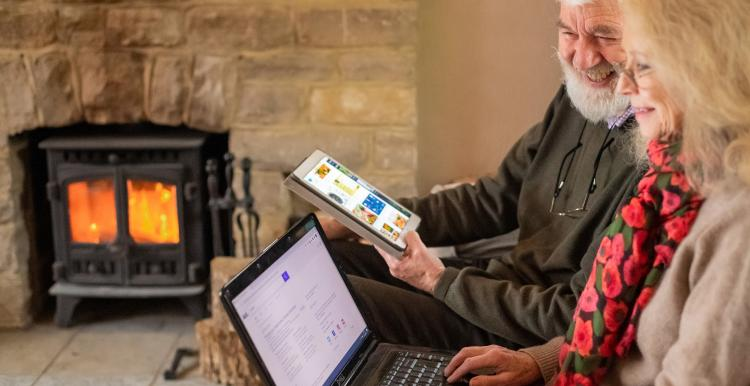 An older couple using a laptop and tablet