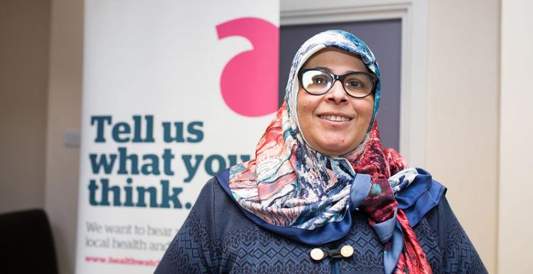 A woman standing infront of a Healthwatch sign that reads 'Tell us what you think'