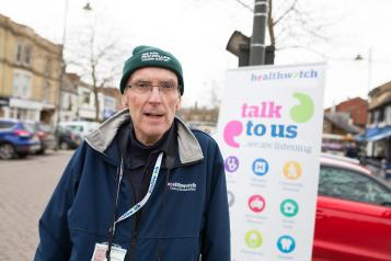 Healthwatch volunteer standing infront of a Healthwatch sign saying 'talk to us'.