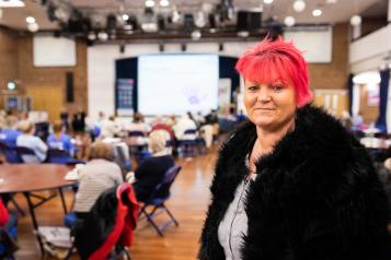 Woman with pink hair at a Healthwatch meeting