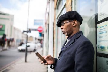 Man standing outside looking at his phone