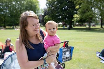 A woman holding her baby in the park. They're both smiling