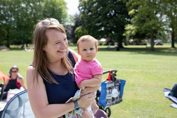 Woman and her baby laughing in a park