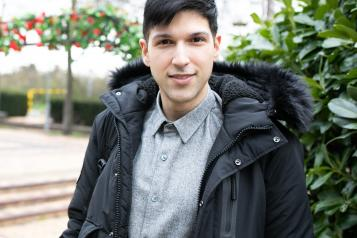 Young man standing outside in a coat