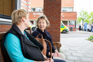Two_Women_Sitting_Outside_Hosptial_Entrance