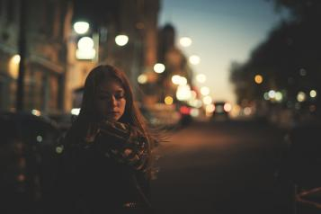 Young woman alone on a street in the dark