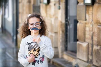 Small child holding up mustache prop for a photograph