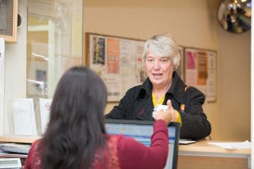 A woman talking to another woman behind a reception desk