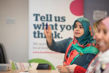 "Woman raising her hand in a focus group, she sits in front of a Healthwatch sign that reads ""Tell us what you think""."