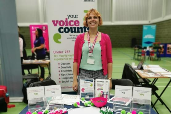 Person standing at a stall greeting potential volunteers