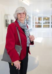 An older woman standing in a hospital corridor. She is wearing a coat and uses a walking stick