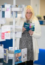 Woman standing in a GP reception area reading leaflets