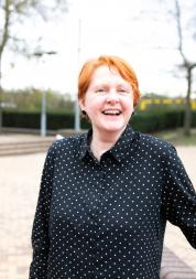 A woman with red hair stands outside laughing