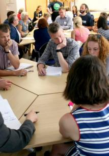 Attendees talking around a table at a Health & Wellbeing Forum