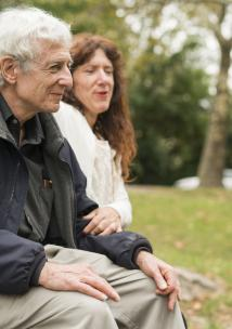 Elderly person sitting on a bench with a friend.