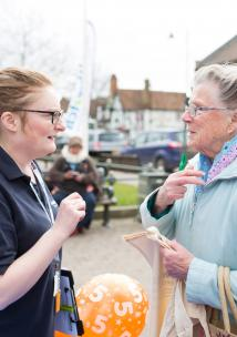 A female volunteer talking to an elderly lady at a community event.